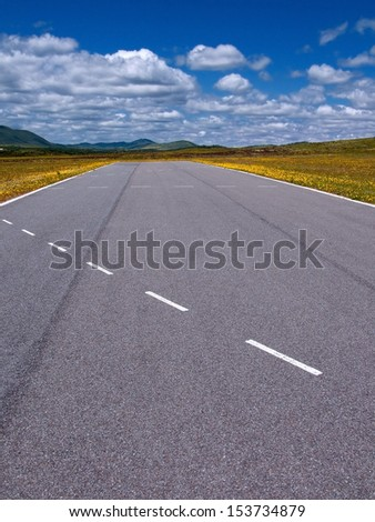 rare highway cut in the middle of the field under blue sky with clouds