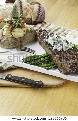 Rare new York strip steak on asparagus topped with bleu cheese with bread and twice baked potato - stock photo