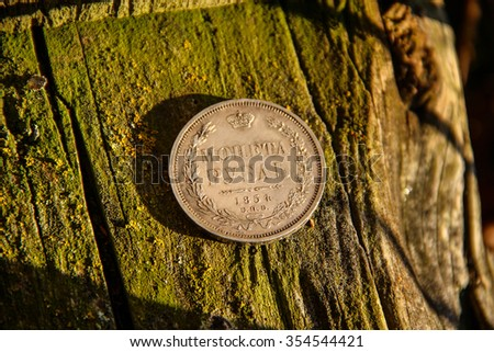 Rare Russian Empire silver ruble coin 1854 on an old wooden stump covered with moss. - stock photo
