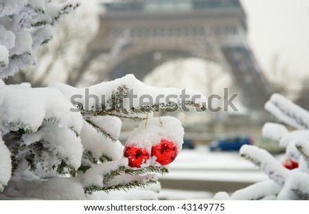 Rare snowy day in Paris. Decorated Christmas tree and the Eiffel tower - stock photo