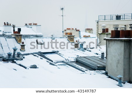 Rare snowy day in Paris. Parisian roofs covered with snow and the Eiffel Tower, view from the Montmartre hill - stock photo