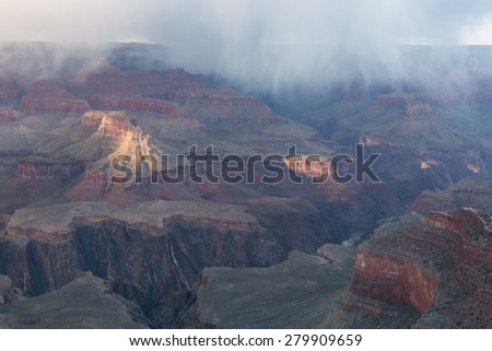 Rare spring shafts of snow moving thru the Grand Canyon from the South Rim - stock photo