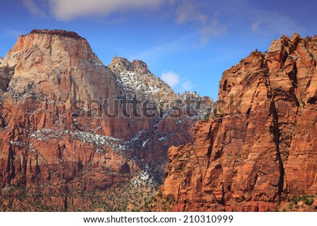 Rare spring snow dusts the top of Zion National Park's West Temple rises high above the Zion Canyon. - stock photo