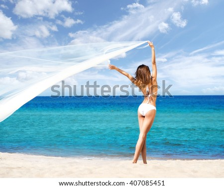 Rare view of hot woman with perfect, seductive legs posing with blowing silk blanket on the beach. - stock photo