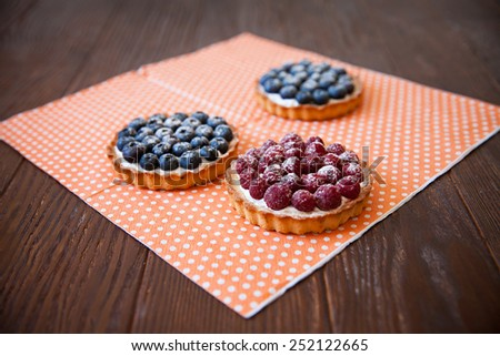 Rasberry and blueberry tartlet on wood - stock photo