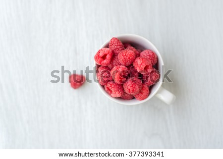 Rasberry in white cup on gray floor with copy space. - stock photo