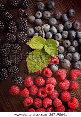 raspberries and blackberry blueberries scattered on the wooden table - stock photo