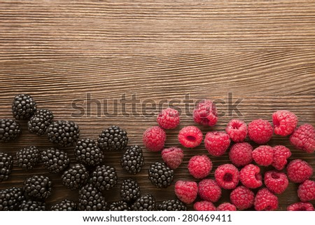 raspberries and blackberry scattered on the wooden table - stock photo