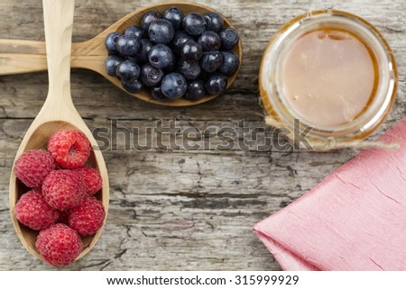 Raspberries and blueberries in spoons with pink napkin and a jar of honey on wooden background. Healthy eating, diet - stock photo