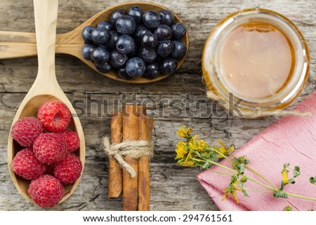 Raspberries and blueberries in spoons with pink napkin and a jar of honey with cinnamon on wooden background. Healthy eating, diet - stock photo