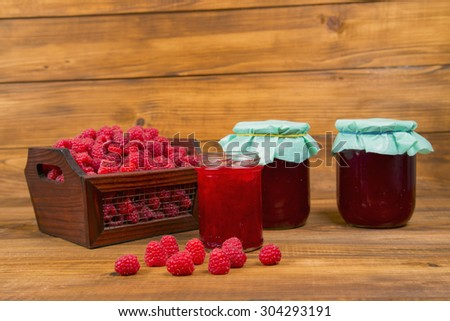 raspberries and raspberry jam on a wooden table - stock photo