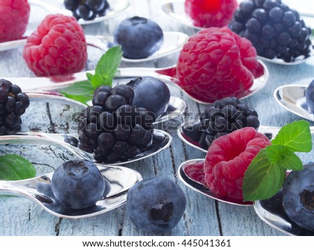 raspberries, blueberries and blackberries on the little spoons with mint leaves - stock photo