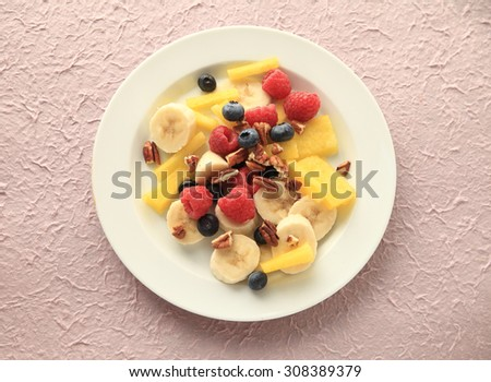 Raspberries, blueberries, yellow watermelon and bananas with chopped pecans on a white plate on a textured pale pink background - stock photo