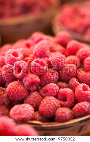 Raspberries for sale in a basket on a market stall - stock photo
