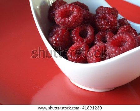 Raspberries in a bowl on red background.
