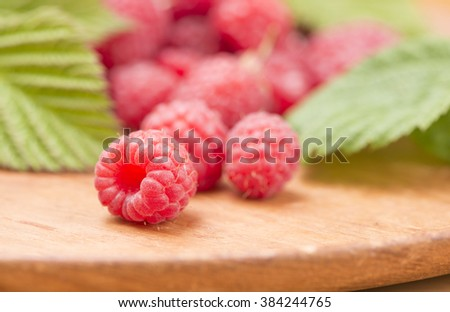 Raspberries in close-up. They are fresh, ripe and red. Tasty food image with juicy berries. - stock photo