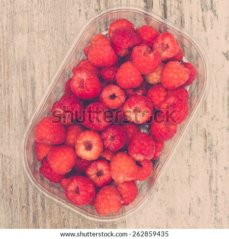 Raspberries in plastic box on wooden table, overhead view, retro filter - stock photo