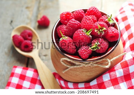 Raspberries in pot on rustic wooden background  - stock photo
