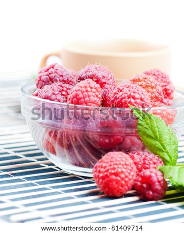 Raspberries with green leafs on the kitchen in high key light - stock photo