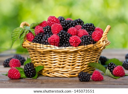Raspberry and blackberry in the basket - stock photo