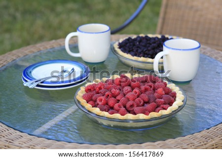 Raspberry and blackberry pie with cups and plates on the table outside.