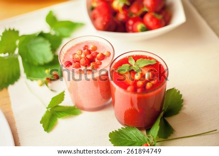 Raspberry and wild strawberry milkshake. Healthy juices. Prepared with fresh fruits. Pieces of fresh fruits. Diet drinks. Presented in glasses and green leaves. - stock photo