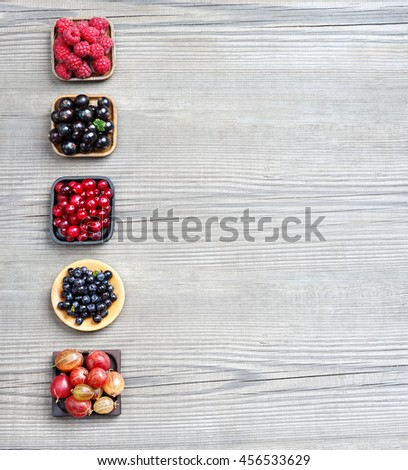 Raspberry, Bilberry, Gooseberry, Cranberry and Currant on wooden background. Top view, high resolution product. - stock photo