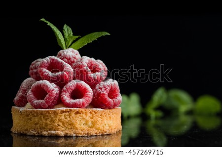 Raspberry cake dessert on dark background. Traditional french sweet pastry tart. Delicious, appetizing, homemade pie with custard, fresh berries and fruits. Copy space, closeup. Selective focus - stock photo