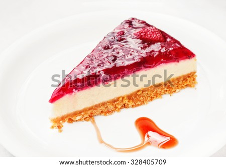 Raspberry cheesecake served on a white plate (shallow dof) - stock photo