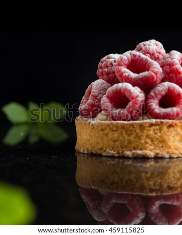 Raspberry dessert cake on dark background. Traditional french sweet pastry. Delicious, appetizing, homemade tart with custard, fresh berries and fruits. Copy space, closeup. Selective focus - stock photo