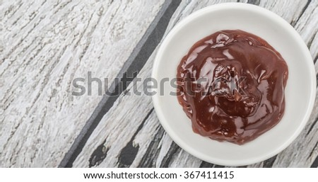 Raspberry fruit curd in white bowl over wooden background