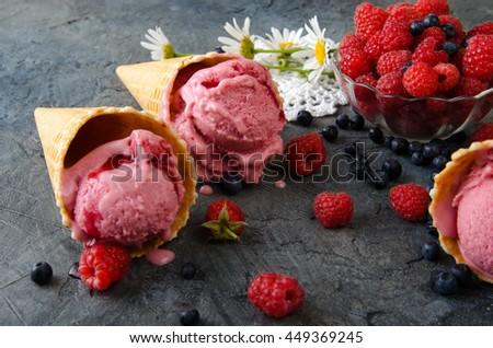 Raspberry ice cream with ice cream cones on stone table. - stock photo