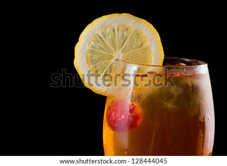 raspberry iced tea garnished with a lemon wheel on a dark bar - stock photo