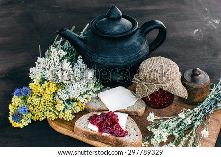 Raspberry jam and bread with butter in a jar and hot herbal tea on the wooden table Lunch breakfast - stock photo