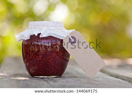Raspberry jam in a jar and fresh berries on the wooden table - stock photo
