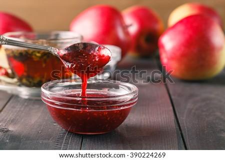 raspberry jam in spoon on dark wooden table - stock photo