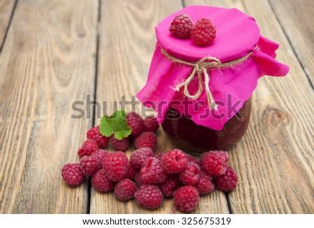 Raspberry jam with fresh raspberries on wooden background - stock photo