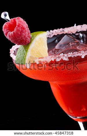Raspberry Margarita in chilled glass over black background on reflection surface, garnished with fresh raspberries and slice of lime. Most popular cocktails series. - stock photo