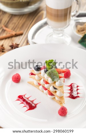 Raspberry mille feuille dessert and cup of coffee on wooden background - stock photo