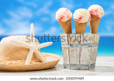 Raspberry ripple ice creams with sunhat and beach blur background - stock photo