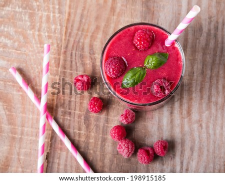 Raspberry smoothie in a glass on wooden table, up view - stock photo