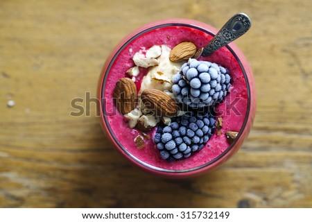 Raspberry smoothie with vanilla ice cream, almonds and blackberries - stock photo
