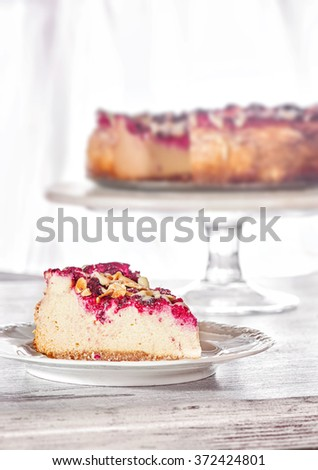 Raspberry tart, cheesecake with fresh raspberries on a white wooden background. Slice of cake with raspberry, almond and white chocolate - stock photo