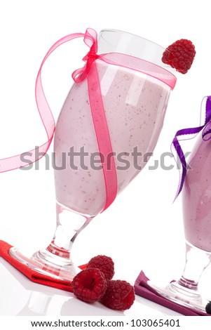 Raspberry yogurt shake with fresh raspberries decorated with pink ribbon isolated on white background. Luxurious summer drinks. - stock photo