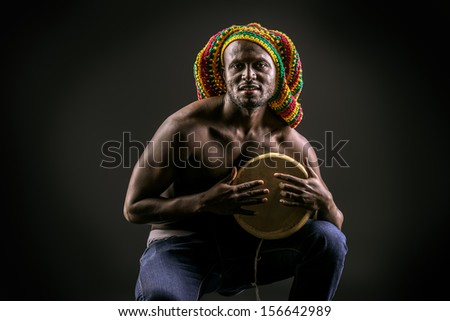 Rastafarian african american man playing his drum. Over dark background. - stock photo