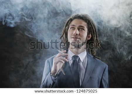 Rastafarian businessman smoking marijuana - stock photo
