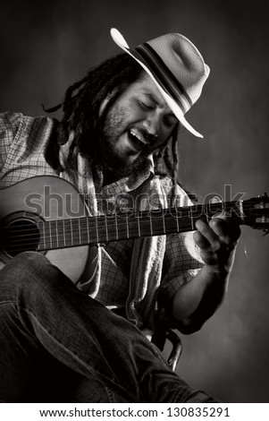Rastafarian man playing classic guitar - stock photo