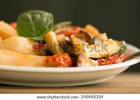 Ratatouille and baked potatoes on white plate against dark background  - stock photo