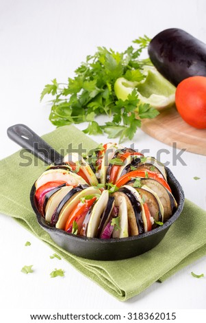 Ratatouille. Baked vegetables (zucchini, tomato, eggplant, onion) in a cast iron pan. - stock photo