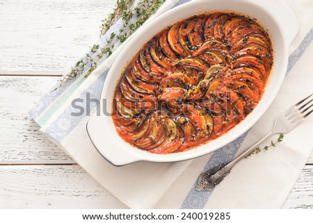 Ratatouille in a baking dish on wooden background - stock photo